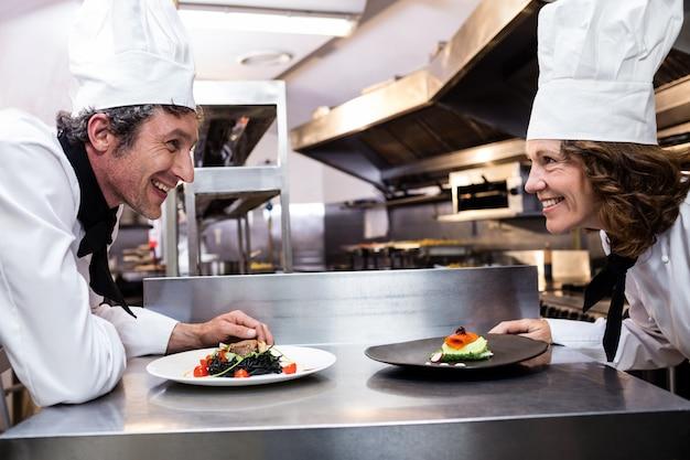 Deux chefs souriants se penchant sur le comptoir avec des assiettes Photo Premium