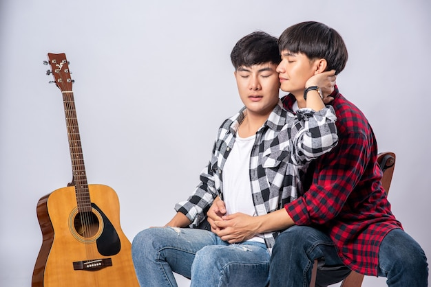 Deux Chers Jeunes Hommes étaient Assis, Câlins Dans Une Chaise Et Avec Une Guitare à Côté. Photo gratuit