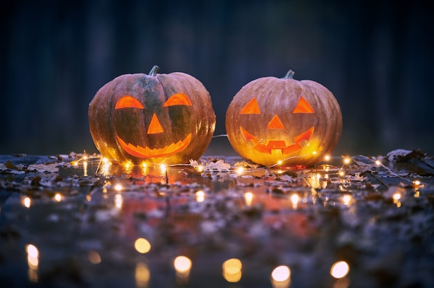 Deux Citrouilles D'halloween Souriant Sur Une Table En Bois Avec Des Lumières Dans Une Forêt Mystique La Nuit Photo Premium
