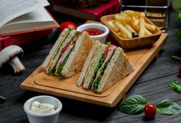 Deux clubs sandwichs au cheddar et au bacon servis avec des sauces et des frites Photo gratuit