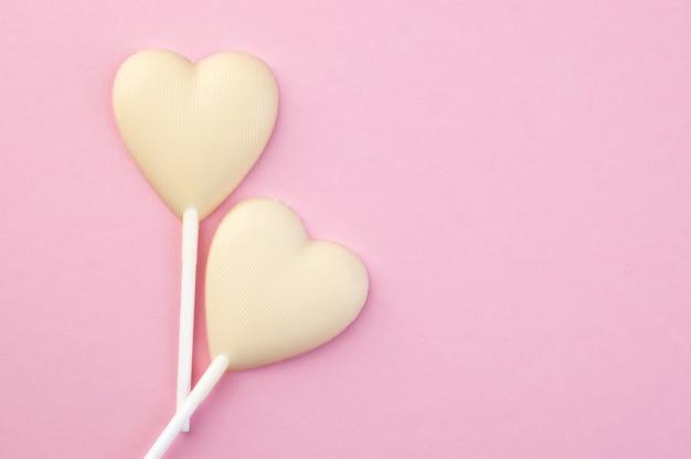 Deux coeurs de bonbons au chocolat blanc sur rose Photo Premium