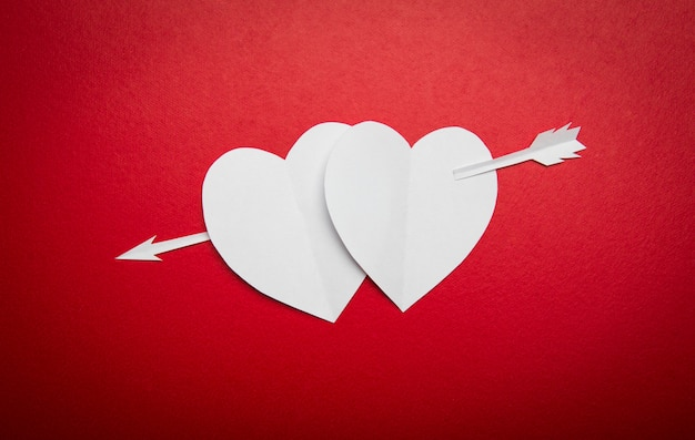 Deux Cœurs En Papier Percés D'une Flèche Pour La St Valentin Photo gratuit