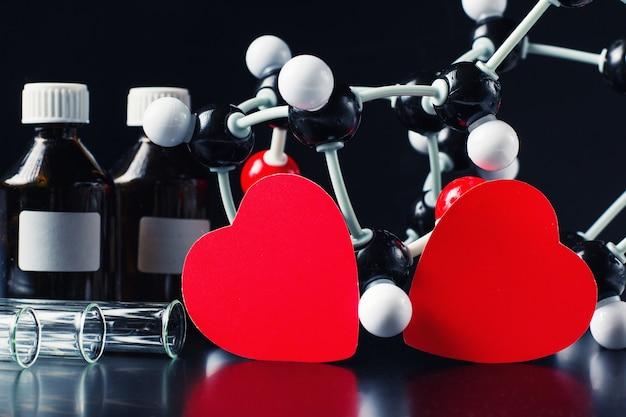 Deux coeurs de papier rouge et modèle de structure moléculaire sur un fond noir. concept de chimie de l'amour Photo Premium