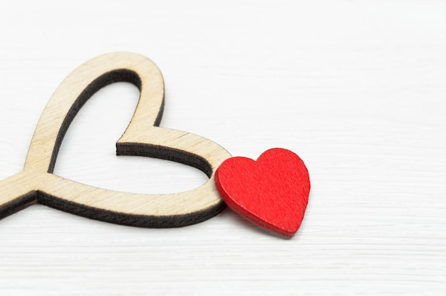 Deux coeurs: petit bois rouge et grand, sur un fond en bois blanc Photo Premium