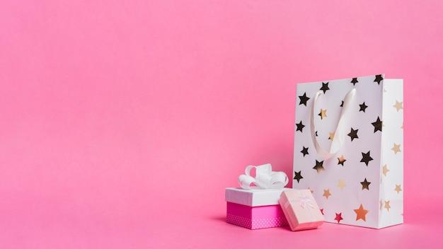 Deux coffrets cadeaux et un sac en papier shopping blanc sur fond rose Photo gratuit
