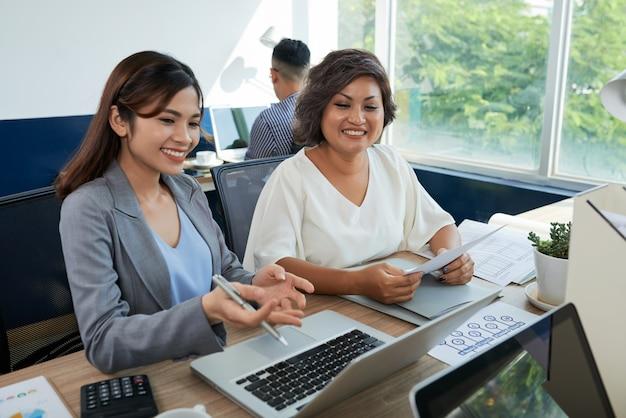Deux collègues asiatiques sont assis au bureau avec un ordinateur portable, une femme aidant une autre Photo gratuit