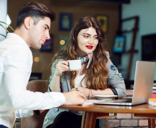 Deux collègues ayant un café et vérifiant un projet dans la zone de repos d'un bureau. Photo gratuit
