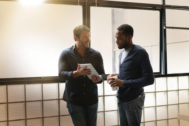 Deux collègues debout ensemble dans un bureau moderne, passant en revue des idées sur une tablette Photo Premium