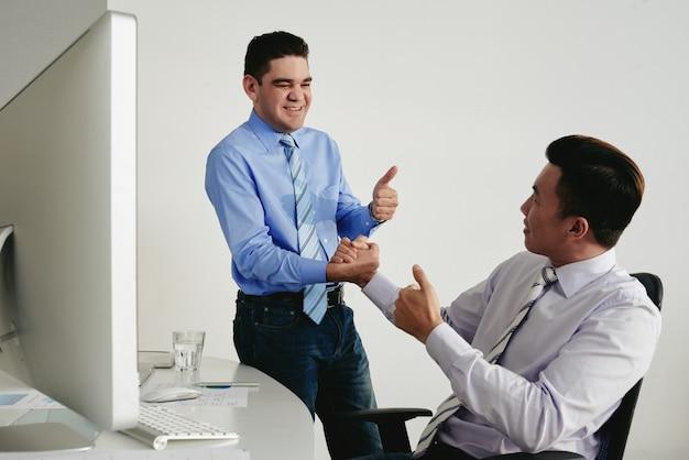 Deux collègues avec le pouce en l'air se serrant la main en signe de bon travail Photo gratuit