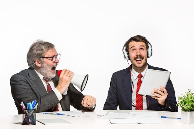 Les Deux Collègues Travaillant Ensemble Au Bureau Sur Fond Blanc. Un Homme Criant à Travers Un Mégaphone - Un Autre Dans Le Casque Ne Peut Rien Entendre Photo gratuit