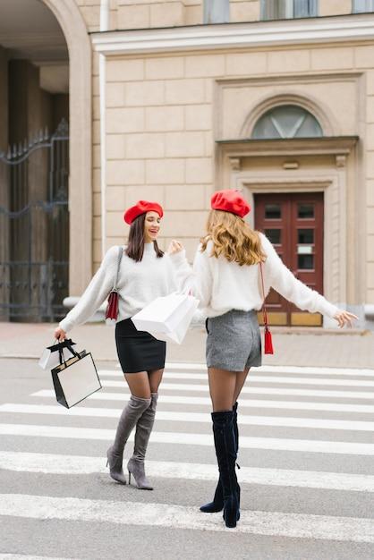 Deux Copines élégantes Avec Des Bérets Rouges Dans Le Style Des Femmes Françaises Sourire Et Rire, Se Promener Dans La Ville, Avec Des Sacs à Provisions Photo Premium