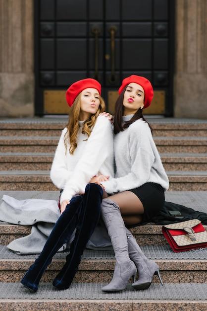 Deux Copines élégantes En Bérets Soufflent Des Baisers Assis Sur Les Marches De La Ville. La Saint-valentin Photo Premium
