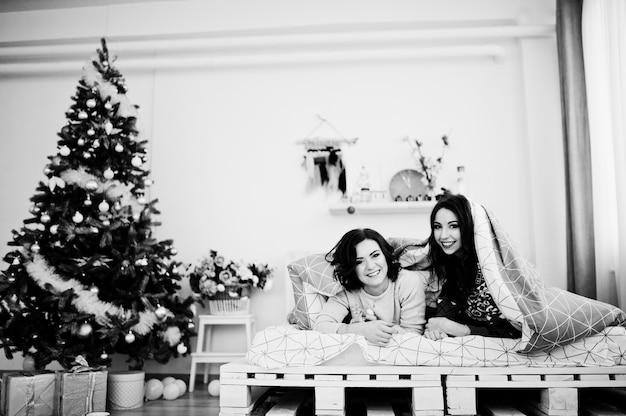 Deux copines portent des chandails d'hiver s'amusant sur un lit dans une chambre avec des décorations de noël. Photo Premium