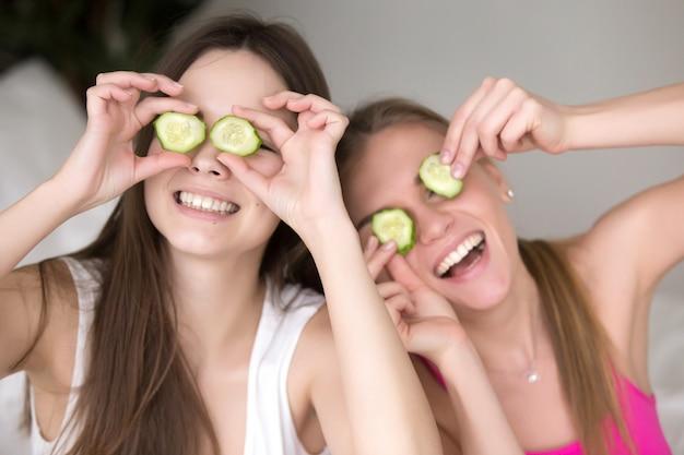 Deux copines sont bêtes en leur mettant des concombres sur les yeux. Photo gratuit