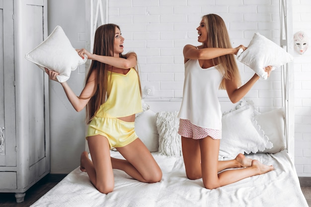 deux-copines-sous-vetements-ayant-bataille-oreillers-dans-chambre_2221-4121.jpg