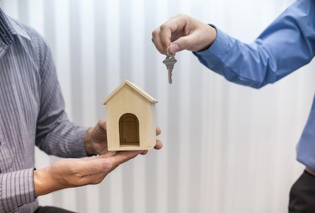 Deux courtiers immobiliers détiennent des clés et des modèles de maison Photo Premium