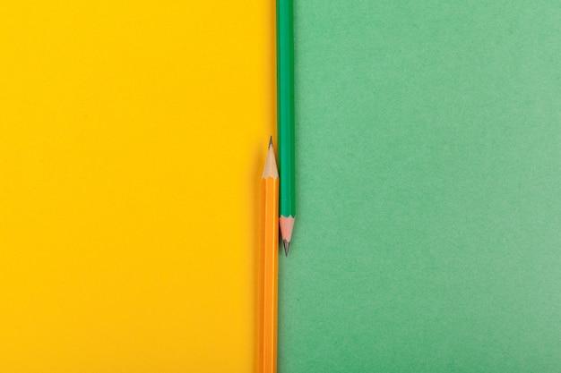 Deux crayons se trouvent à la jonction de deux papiers colorés, vue de dessus verte et jaune Photo Premium