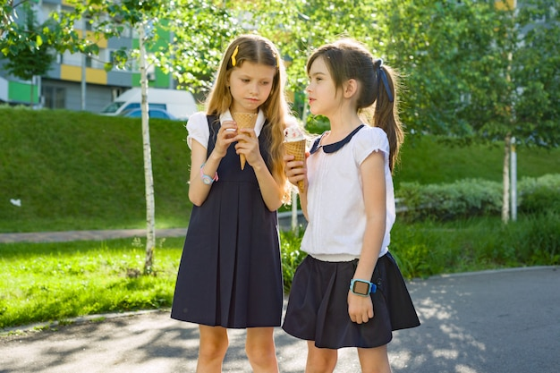 Deux écolières en uniforme scolaire, manger de la glace. Photo Premium