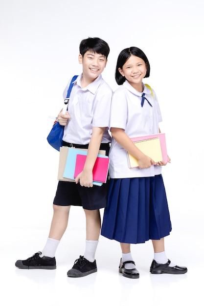 Deux écoliers Asiatiques Souriants Avec De La Papeterie Colorée, Photo Premium