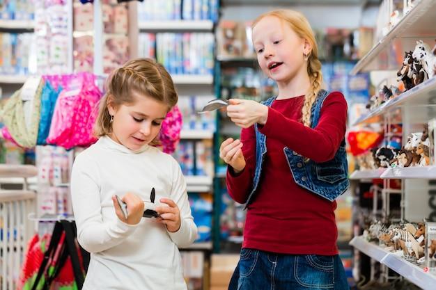 Deux enfants achètent des jouets dans un magasin de jouets Photo Premium