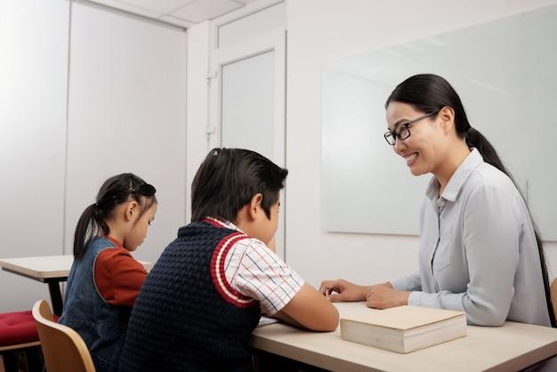 Deux, Enfants Asiatiques, Assis Dans Classe, Et, Sourire, Prof, Dans, Lunettes, Parler, à, Garçon Photo gratuit