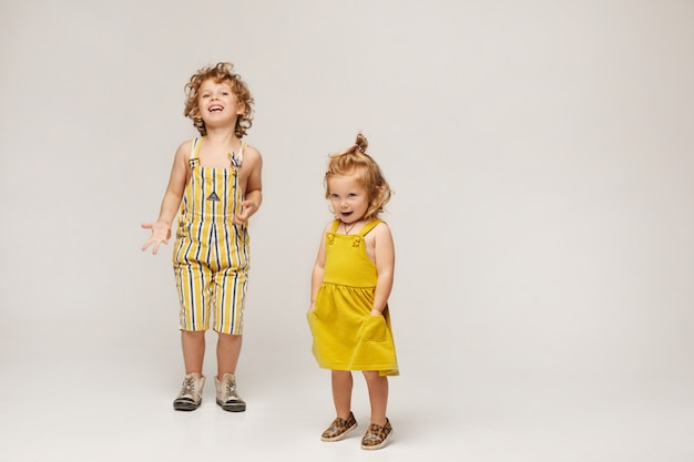 Deux Enfants élégants Mignons, Garçon Et Fille Dans Des Vêtements D'été à La Mode Posant Sur Un Fond Beige. Isolé En Pleine Longueur Avec Espace Copie Photo Premium