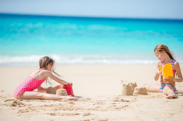 Deux enfants faisant un château de sable et s'amusant à la plage tropicale Photo Premium