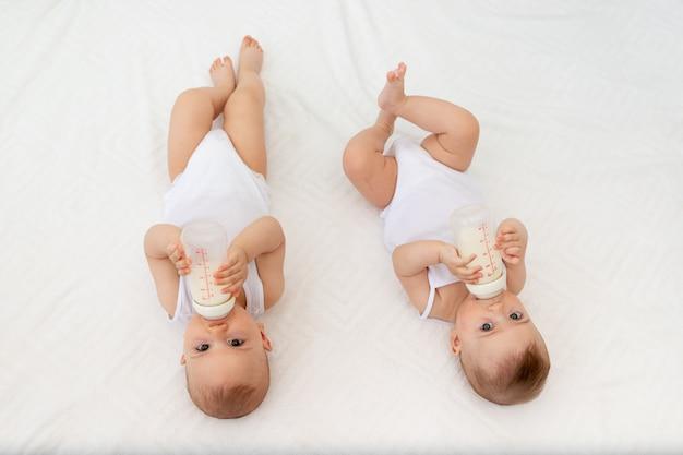 Deux Enfants Un Garçon Et Une Fille-jumeaux De 8 Mois Boivent Du Lait D'une Bouteille Sur Le Lit Dans La Crèche, Nourrir Le Bébé, Concept D'aliments Pour Bébé, Vue De Dessus Photo Premium