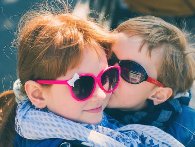Deux Enfants Mignons Avec Des Lunettes De Soleil. Garçon Embrasser Fille Photo Premium