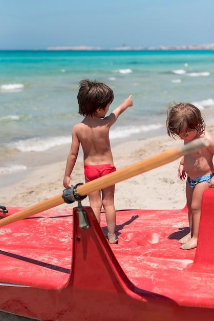 Deux Enfants à La Plage Debout Sur Le Pédalo Photo gratuit