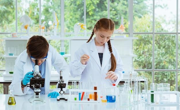 Deux enfants scientifiques faisant des expériences chimiques avec un microscope à la recherche dans la salle de laboratoire. Photo Premium