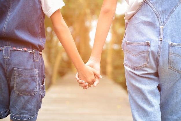 Deux Enfants Se Tenant La Main Sur Le Chemin En Bois Photo Premium