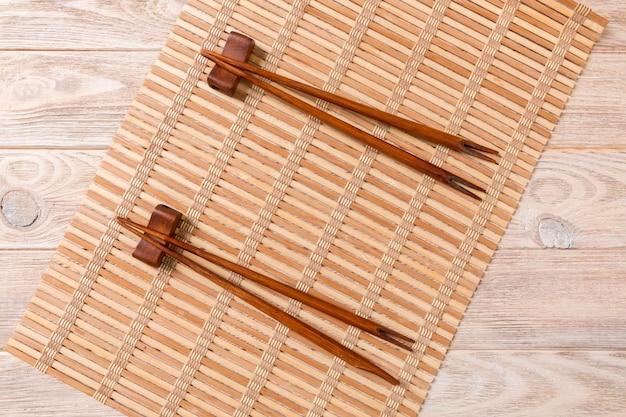 Deux ensembles de baguettes de sushi sur du bambou en bois Photo Premium