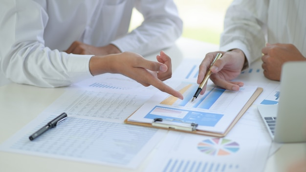 Deux équipes Commerciales Discutent Et Analysent Les Graphiques Du Projet Travaillant Ensemble Au Bureau. Photo Premium