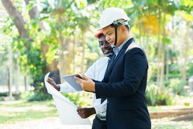 Deux équipes d'experts en architecture et ingénieur architectes asiatiques et africains préparent un sourire dans la nature verdoyante Photo Premium