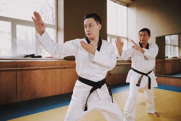 Deux étudiants en arts martiaux s'entraînant à faire du karaté. Photo Premium