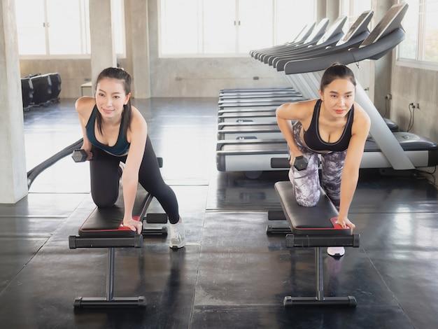Deux femme exerce avec un haltère dans la salle de gym Photo Premium