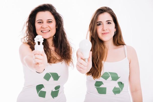 Deux, femme, porter, recycler, icône, tanktop, projection, fluorescent, ampoule Photo gratuit