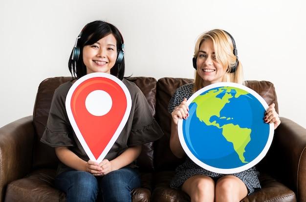 Deux femme tenant un icone de localisation Photo Premium