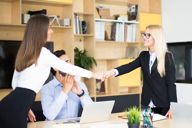 Deux femmes d'affaires se serrant la main sur un bureau alors qu'elles concluent un accord ou un partenariat Photo Premium