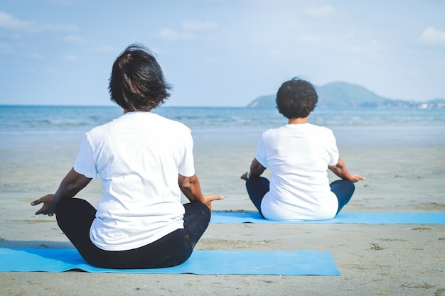 Deux Femmes âgées Assises Sur Le Sable, Faisant Du Yoga En Bord De Mer Photo Premium