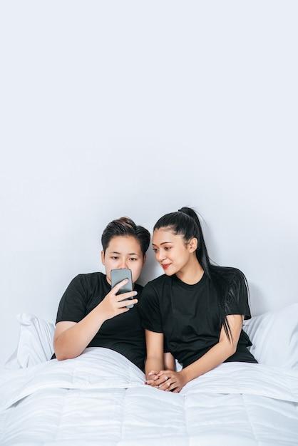 Deux Femmes Aimantes Qui Dorment Et Jouent Aux Smartphones. Photo gratuit