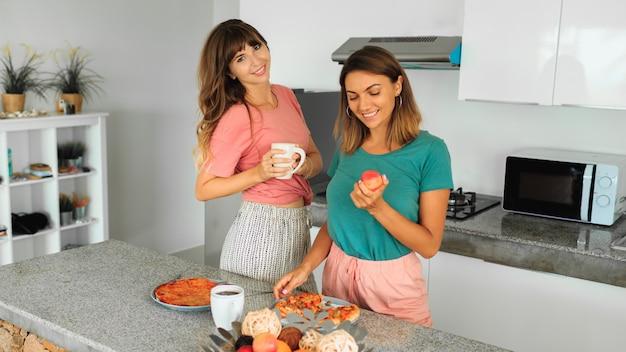 Deux Femmes Appréciant La Pizza Dans La Cuisine Dans Un Appartement Moderne. Photo gratuit