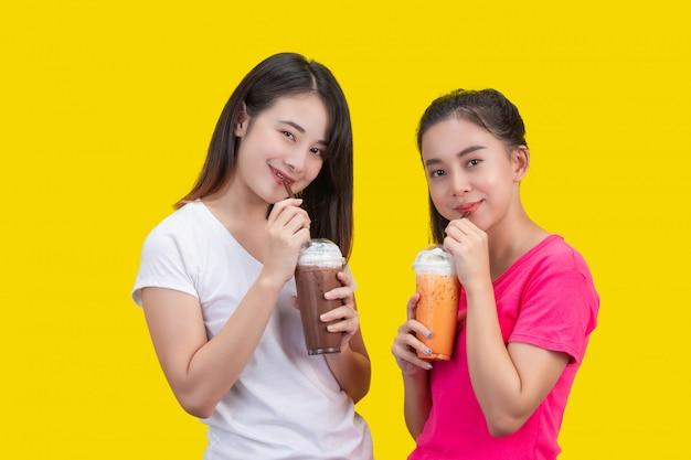 Deux femmes asiatiques buvant du thé au lait glacé et du cacao glacé sur un fond jaune. Photo gratuit
