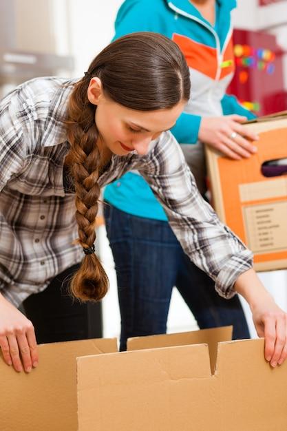 Deux femmes avec une boîte de déménagement dans sa maison Photo Premium