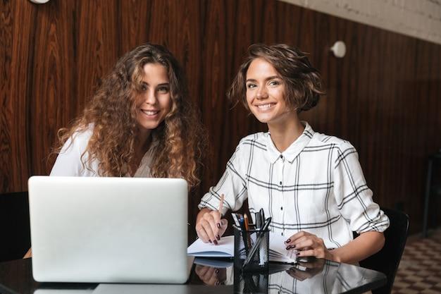 Deux Femmes Bouclées Souriantes Travaillant à La Table Photo gratuit