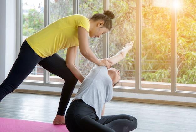 Deux femmes en classe, exercice de relaxation ou cours de yoga après l'entraînement près du studio de la fenêtre Photo Premium