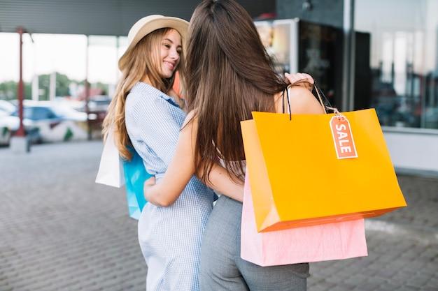 Deux femmes étreindre faire du shopping Photo gratuit