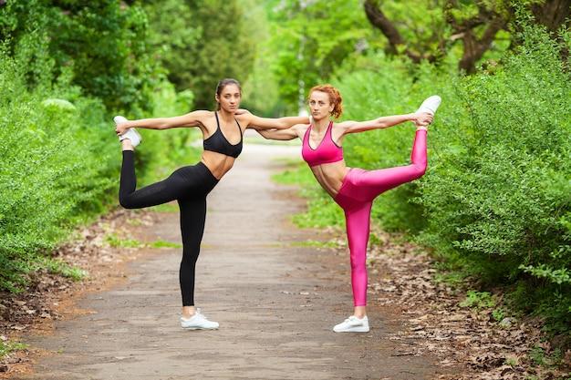 Deux femmes exerçant dans le parc. belle jeune femme faisant des exercices en plein air Photo Premium