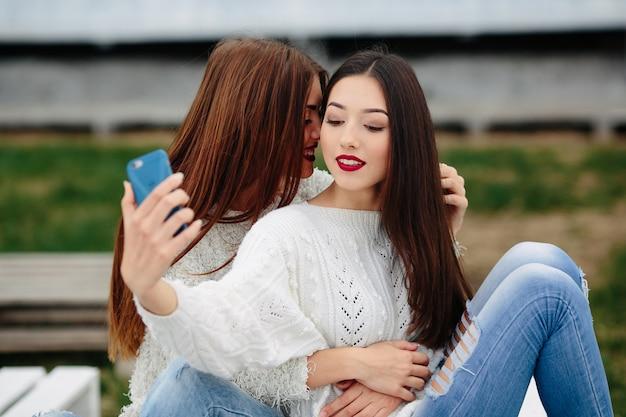 Deux Femmes Faisant Selfie Sur Le Banc Dans Le Parc Photo gratuit